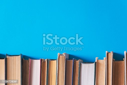 istock old books on bookshelves with blue background 1154728391