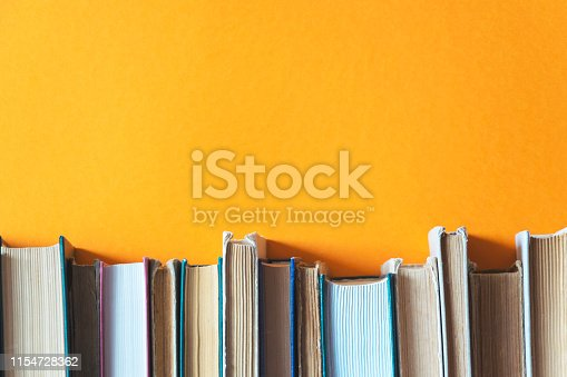 old books on bookshelves with orange background