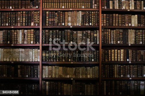 Old books organised in a library bookshelf.