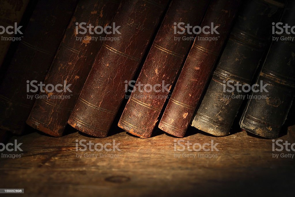 Old Books Stack of old books in a row on wooden surface Art Stock Photo