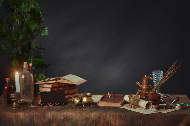 Old books, scrolls, pen and inkwell, antique objects made of gold and brass on a dark background. Space for your text. stock photo