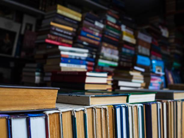 alte bücher stehen hintereinander auf einem regal in einer buchhandlung. viele bücher mit klassischer literatur - gebrauchte bücher verkaufen stock-fotos und bilder