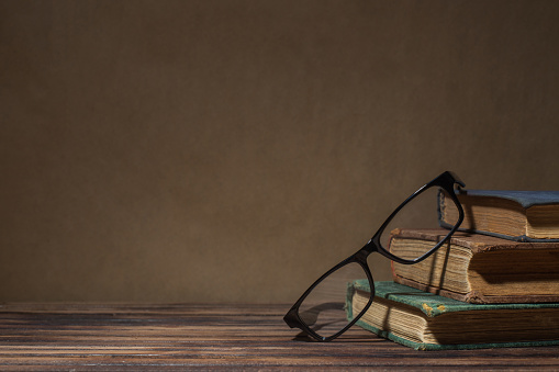 Old books with glasses on table