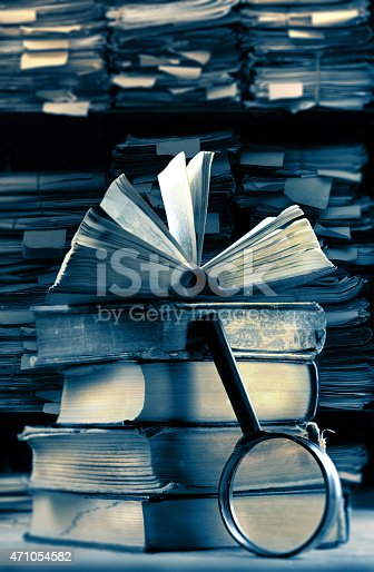 668340340istockphoto Old books with magnifying glass 471054582