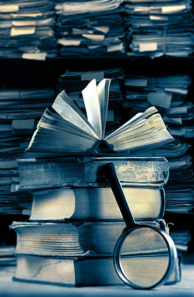 Old books with magnifying glass stock photo