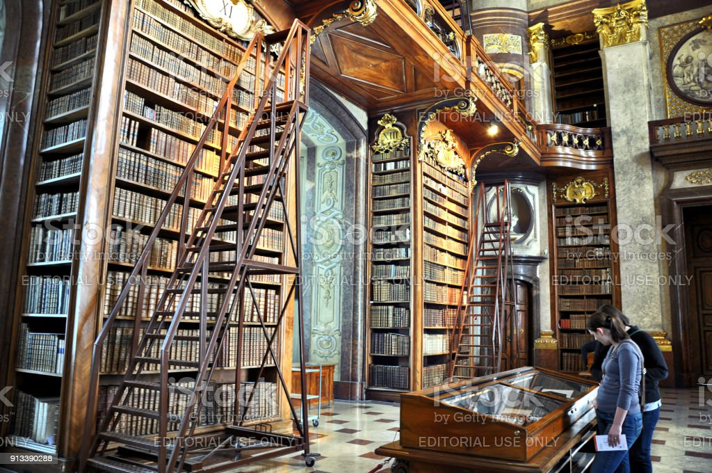 Old bookshelfs with ladder and books inside the famous Austrian National library. stock photo