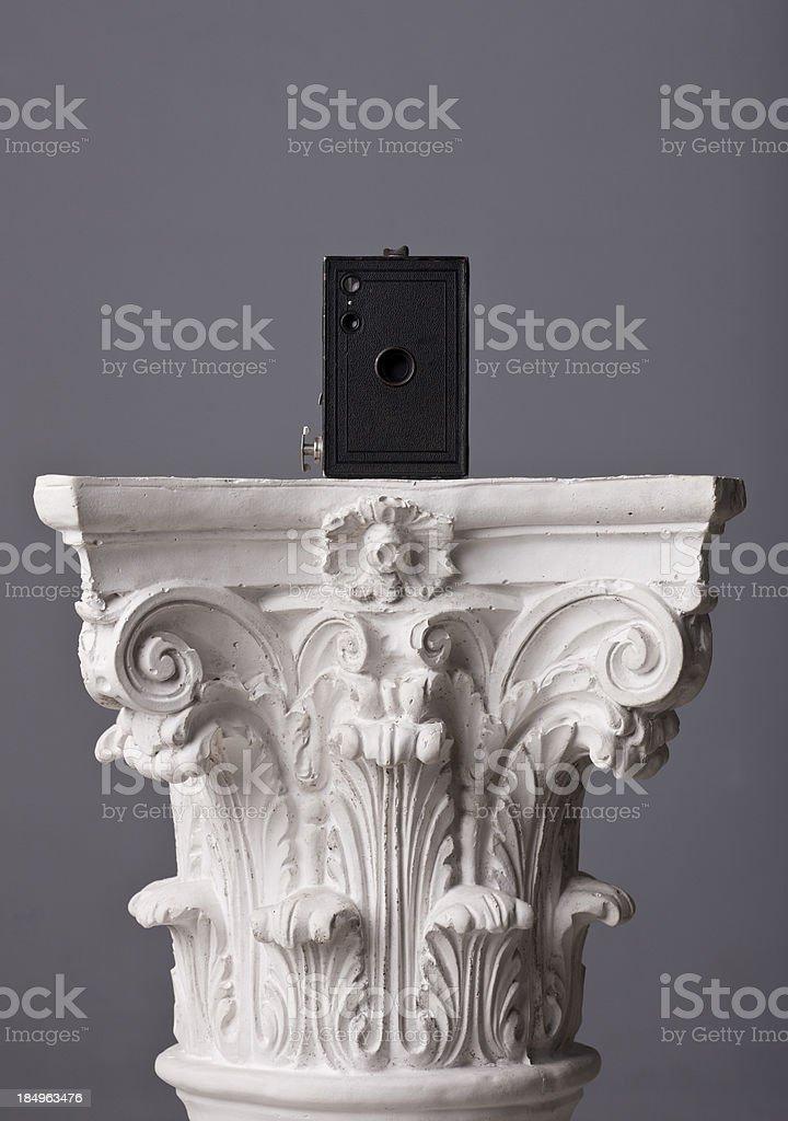 old box camera on a corinthian capital royalty-free stock photo
