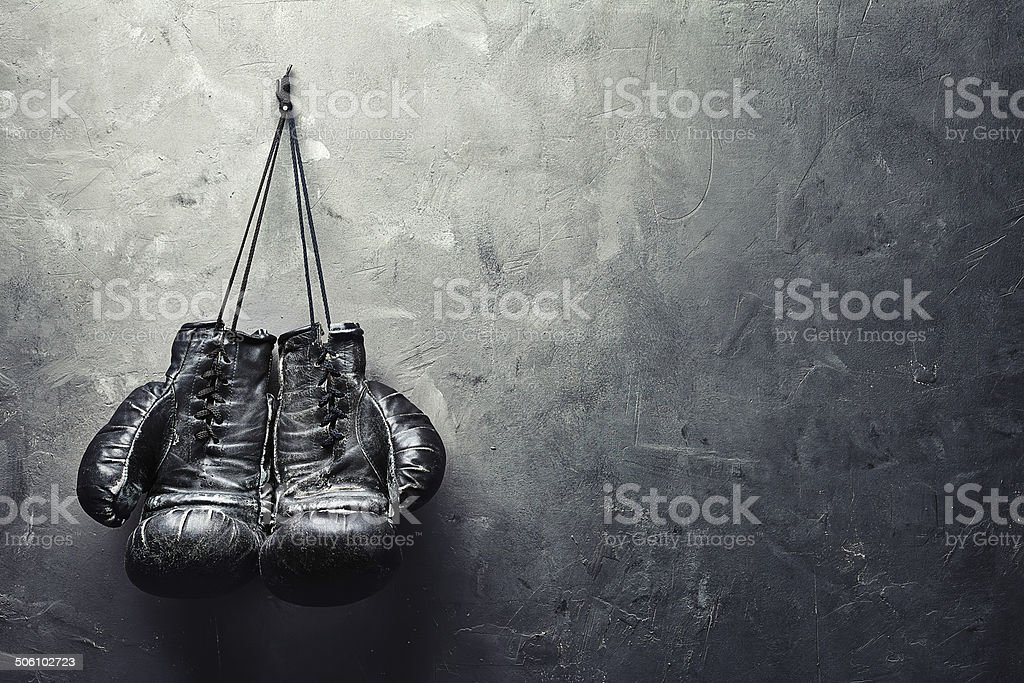 old boxing gloves nailed to the textured wall stock photo