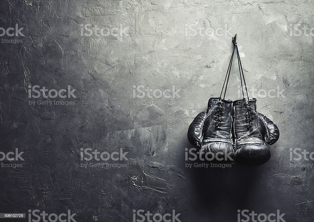 old boxing gloves nailed to the textured wall stok fotoğrafı
