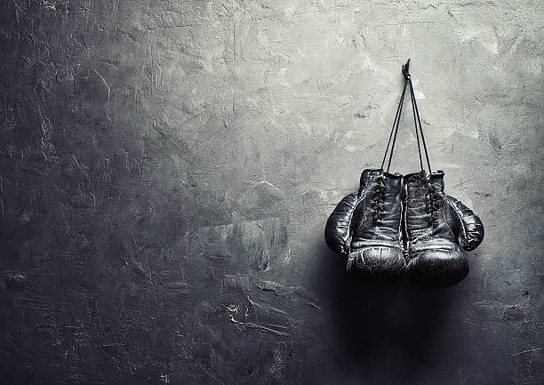 old boxing gloves nailed to the textured wall - endurance stock pictures, royalty-free photos & images