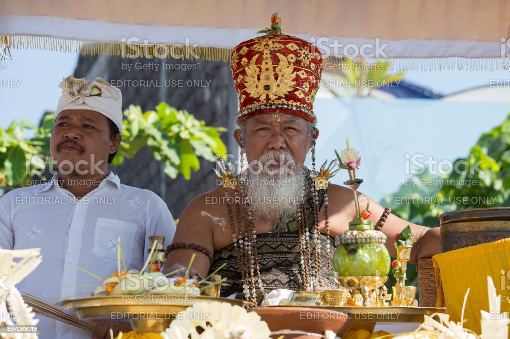 Old Brahmin conducts religious ritual on the beach Ketewel. Bali, Indonesia stock photo