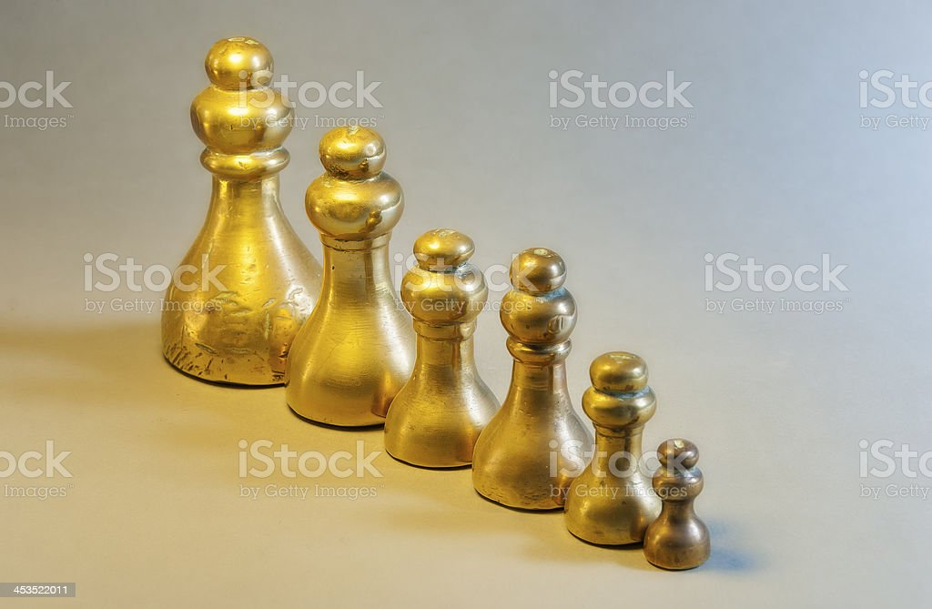 Old Brass Weights in line, largest to smallest royalty-free stock photo