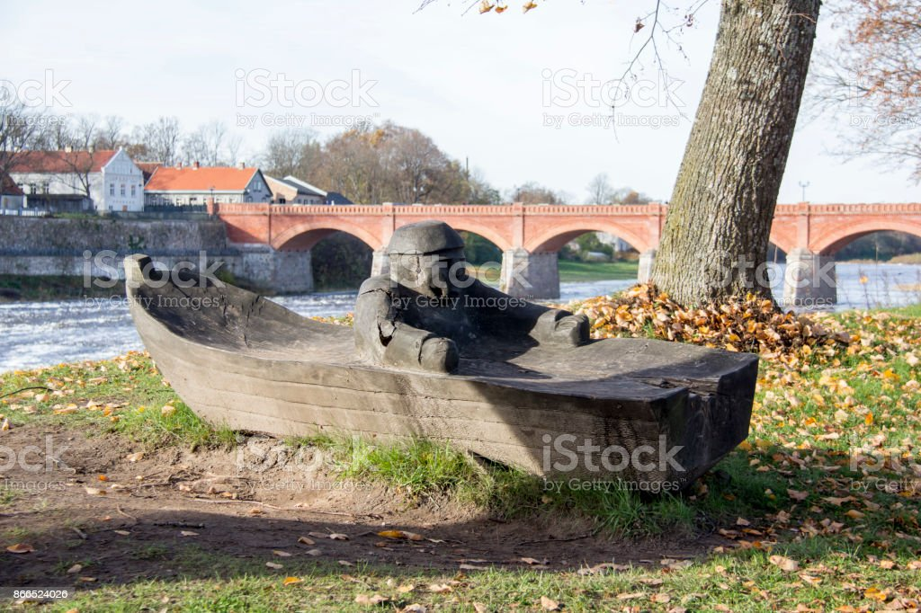 old Brick bridge across the River Venta in the city of Kuldiga Latvia and fisherman in the boat wooden figure stock photo