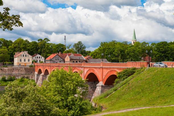 Old brick bridge over Venta river in Kuldiga, Latvia. Summer time. stock photo