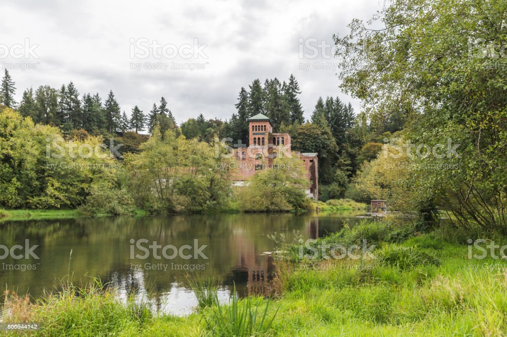 Old Brick Building Near Lake in Green Area stock photo