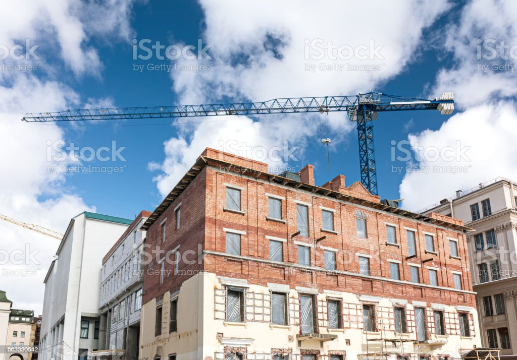 old brick building under reconstruction with tower crane on blue sky background stock photo