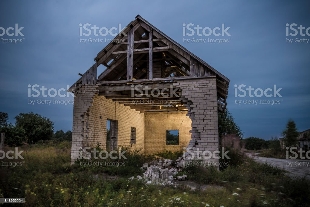 Old brick house with one wall collapsed stock photo
