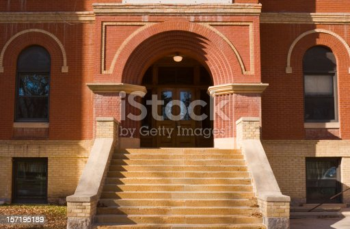 Horizontal straight-on exterior view of an old red brick high school or elementary schoolhouse building facade, centered on the entrance front door and staircase.  The traditional architecture suggests a respect for higher education and learning. The brownstone built structure is located in a small Midwestern town in the U.S.A.