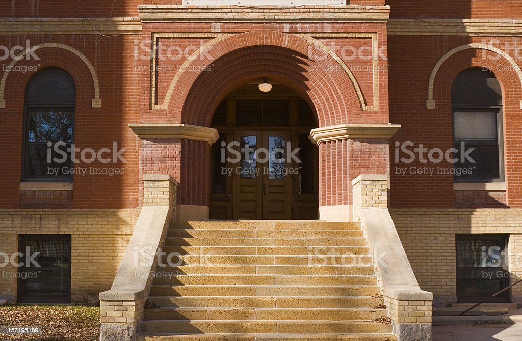 Old Brick School Building Exterior Front Entrance Door and Steps stock photo