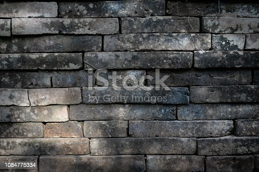 611897876 istock photo Old brick wall background with light 1084775334