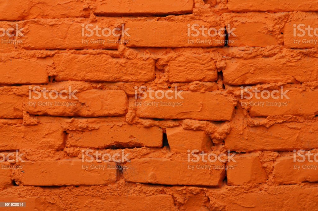 Old brick wall painted in orange color stock photo