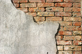 Old red brick wall exposed in corner through concrete.