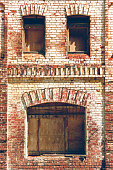Old brick wall with boarded up windows. Old warehouse, retro city architecture. Brickwork of destroyed and weathered bricks with window openings.
