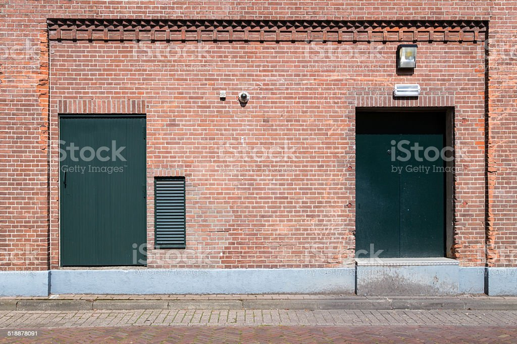 Old brick wall with green doors and street stock photo