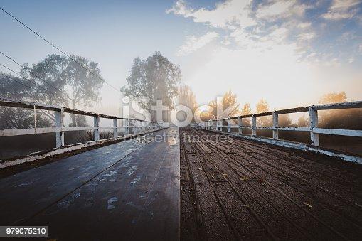 istock Old bridge in fog sunrise 979075210