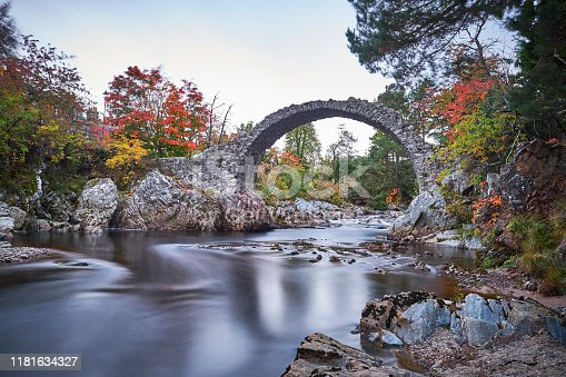 Old bridge in scotland where the river flows underneath the rocks in the fall.