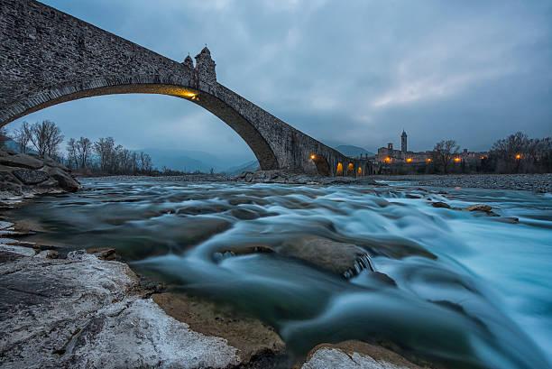 old bridge con archs sul fiume, bobbio, italia - bobbio foto e immagini stock