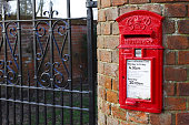 Buckingham, UK - January 16, 2016. A traditional British post box is set into a wall outside a house in Buckinghamshire. The post box dates from the reign of George VI from 1936 to 1952.