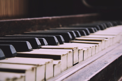 Old broken disused piano with damaged keys Vintage Retro Filter.
