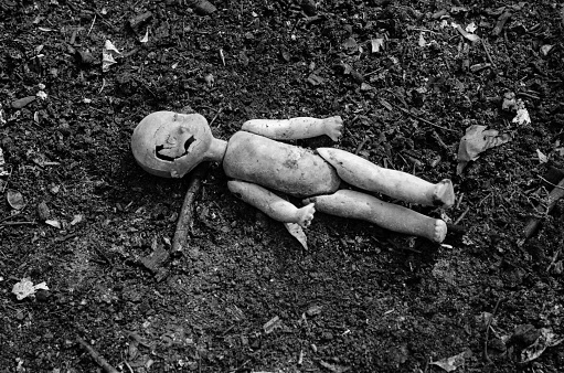 Old broken doll on the pile of the ash