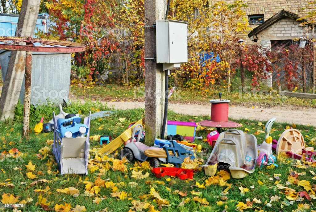 Old broken forgotten outdoor  no name  children toys on autumn village lawn near electrical box. royalty-free stock photo