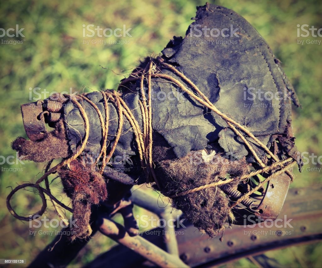 old broken saddle of a bicycle fixed with string stock photo