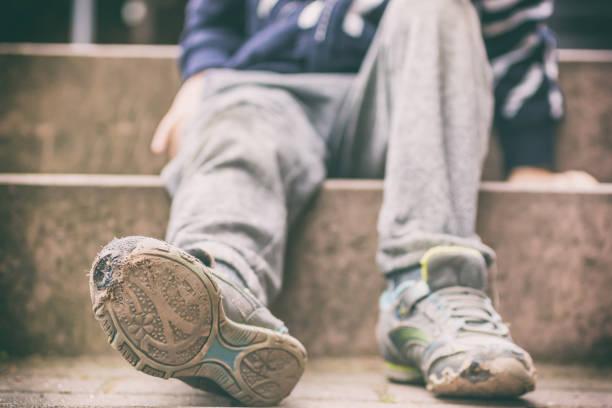 Alte Schuhe eines kleinen Jungen als Symbol für Kinderarmut gebrochen – Foto