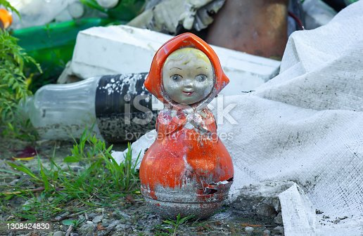 Old broken ussr roly-poly doll garbage lying on ground in summer park
