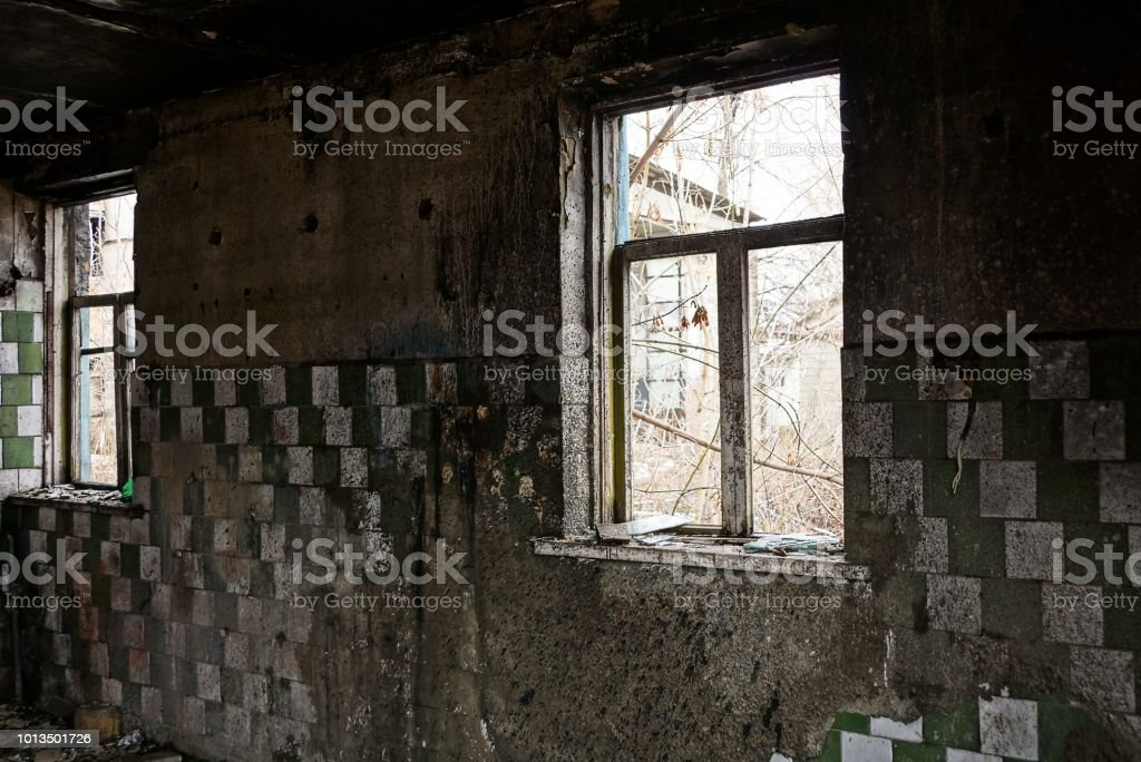 old broken windows in the charred dirty room of an abandoned building