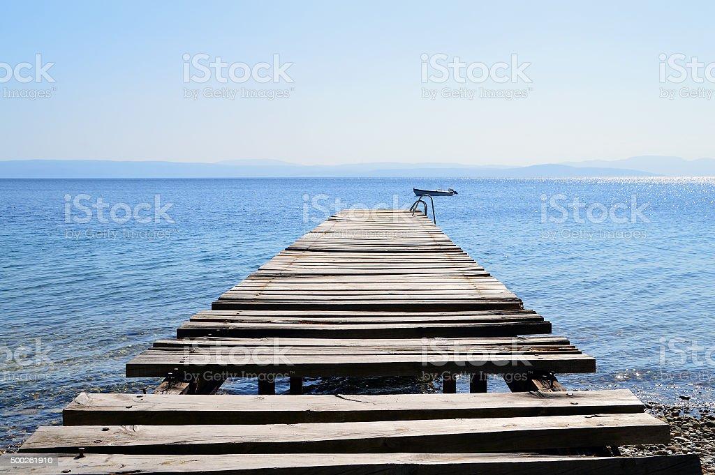 Old broken wooden pier in calm blue sea stock photo