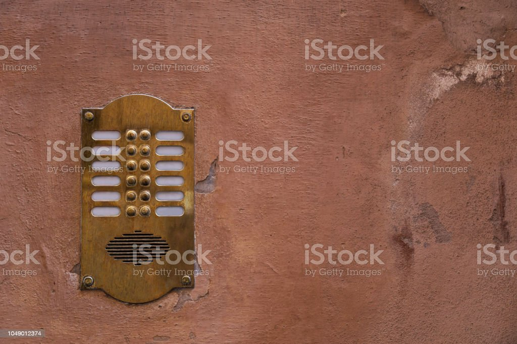 Old bronze intercom on an old wall with peeling paint stock photo