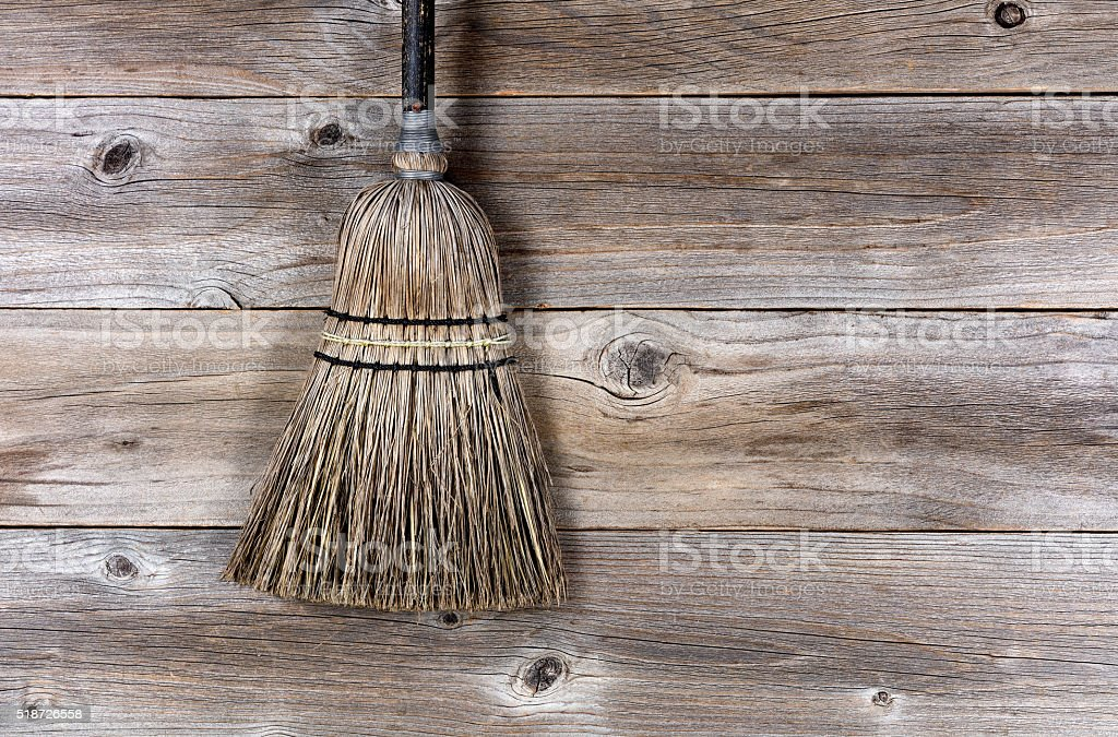 Old broom laying on rustic wooden boards stock photo