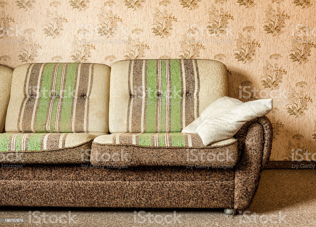 Old brown and green three-seat couch in a living room stock photo