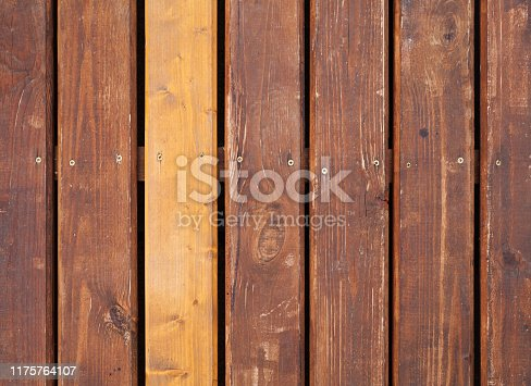 Old brown outdoor wooden floor with one new board, background photo texture