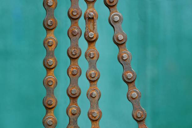 old brown rusty bicycle chain on a green background stock photo