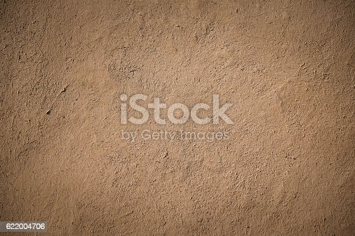closeup detail of old brown stucco clay wall, rough surface background or backdrop in architectural material concept