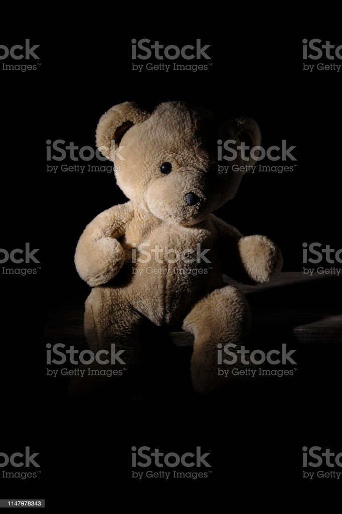 old brown teddy bear is sitting on a wooden surface, balck background