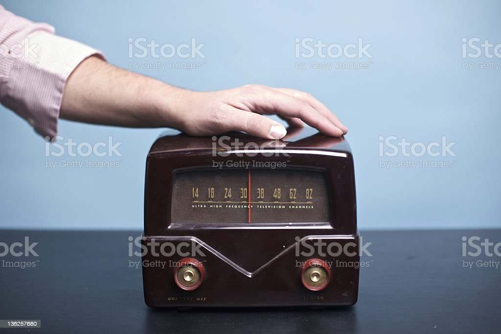 Old Brown Vintage Radio with a Male Hand on Top stock photo