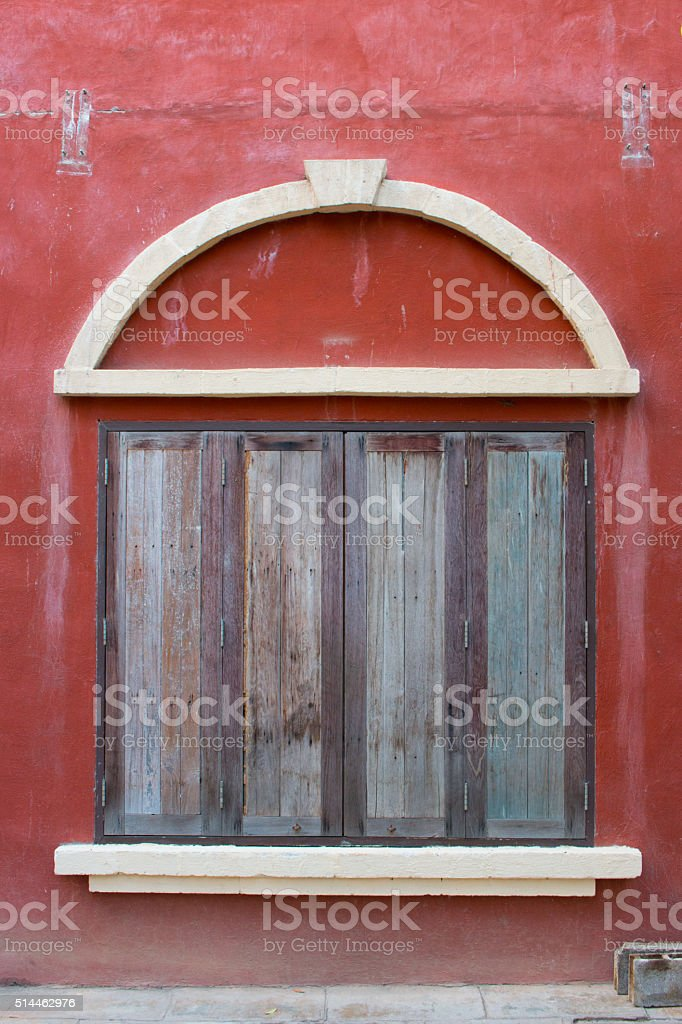 old brown wooden window with red background stock photo