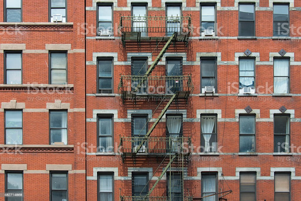 Old brownstone apartment building with an iron fire escape stairs stock photo
